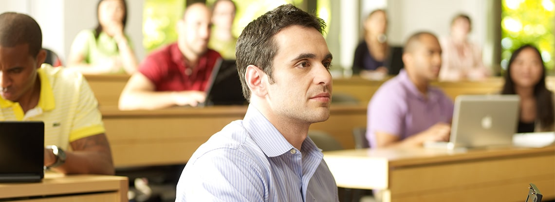 A young professional sits in a lecture hall and looks up at a speaker off camera.