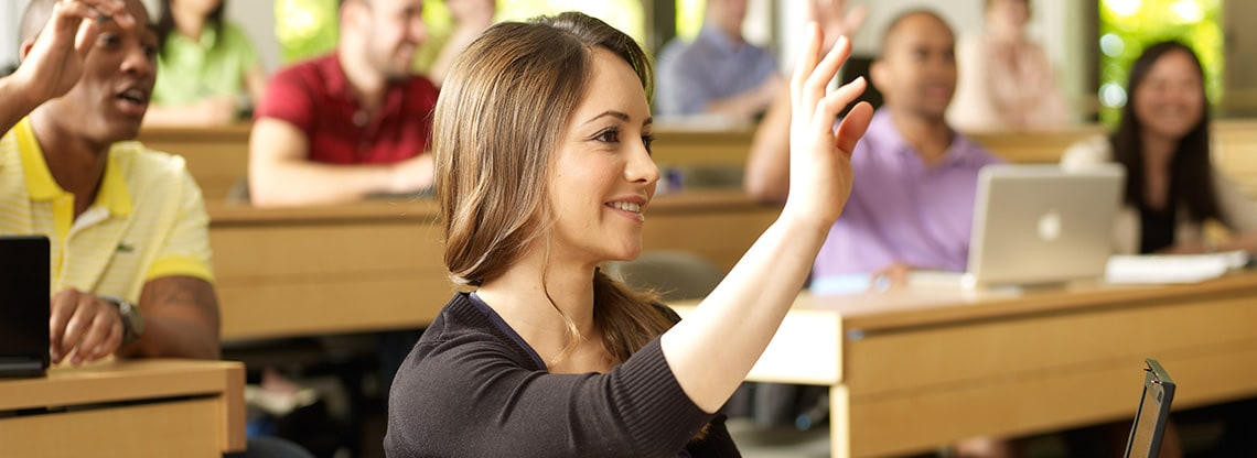 A young woman raises her hand in a lecture hall filled with other participating students.