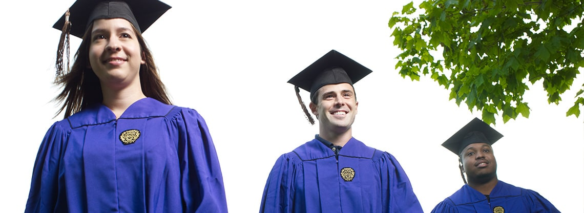 Three Kellogg graduates wearing regalia stand tall against a clear sky.